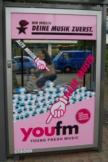 Ein Schlitz in der Glasvitrine ermöglicht es alte CDs in das City-Light-Poster zu werfen