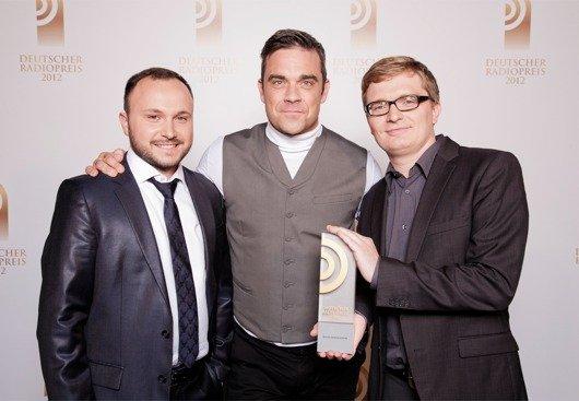 Laudator Robbie Williams mit Preisträger Christian Bollert und Marcus Engert (detektor.fm) (Bild: NDR)