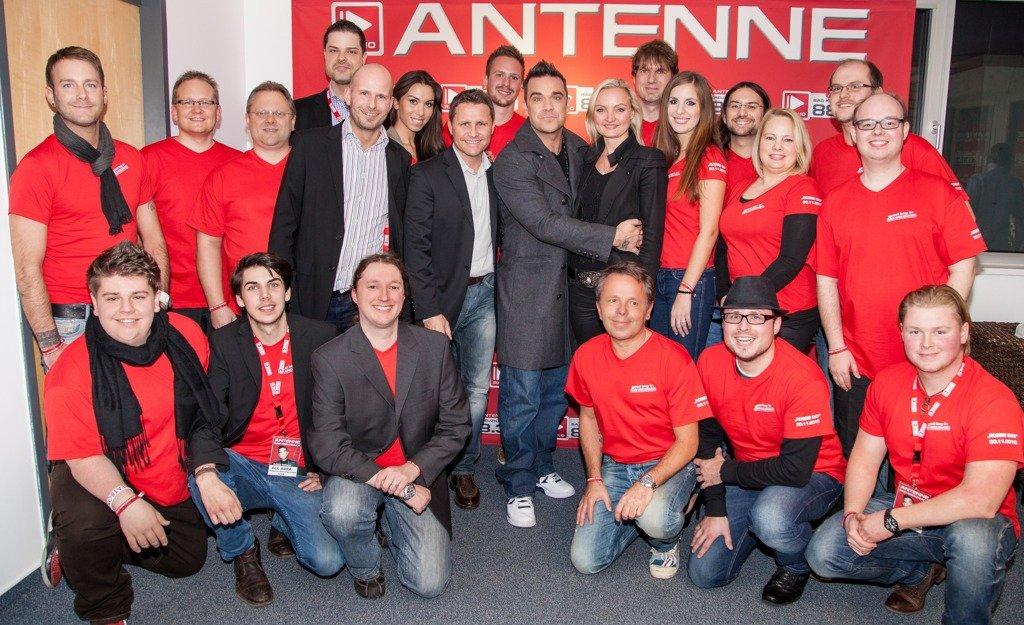 Robbie Williams zwischen Geschäftsführerin Doreen Gesierich, die er spontan in den Arm nahm,  Stephan Schwenk - Chef der Radiogroup und dem Antenne Bad Kreuznach Team