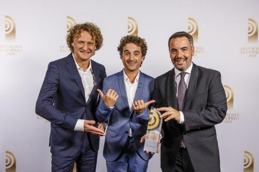 Marco Brandt und Matthias Pfaff (Radio PSR) sind Gewinner des Radiopreises 2015 in der Kategorie 'Beste Innovation'. Hier mit Laudator Oliver Wnuk. Foto: Deutscher Radiopreis/Morris Mac Matzen