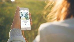 Ein Smartphone mit der Bayern 2 App auf einem Holzboden (Bild: BR/Max Hofstetter)