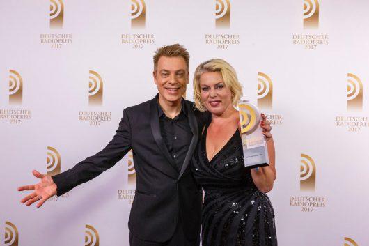 """Laudator Michael Mittermeier hat den Preis für die """"Beste Moderatorin"""" an Gerlinde Jänicke von 94,3 rs2 überreicht. (Bild: Deutscher Radiopreis/Morris Mac Matzen)"""