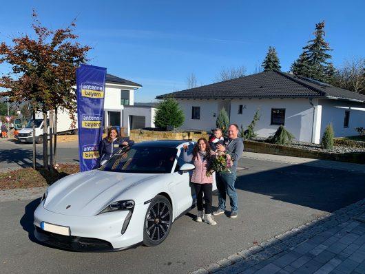 Stefanie Kaatzke (2. v.r.) und ihre Familie aus Eschenbach freuen sich über ihren neuen Porsche Taycan von ANTENNE BAYERN, den Moderatorin Marion Schieder (links) in die Oberpfalz gebracht hat. (Bild: ©ANTENNE BAYERN)